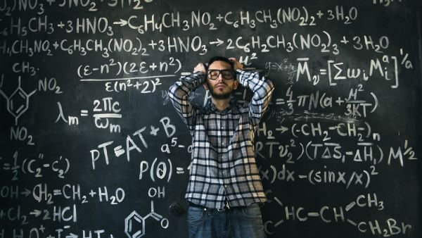 A man puzzles over complicated equations involved in calculating earned income.